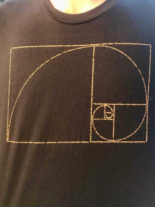 A close up look at our Golden Ratio design on a mens crew neck t-shirt in black. The design is made from tiny, positive quotations about the connection between Phi and the universe!